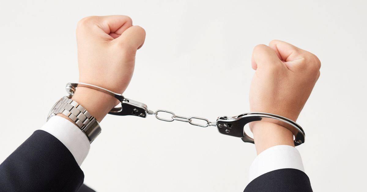 手錠をかけられたスーツ姿の男性の腕