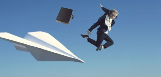 巨大な紙飛行機から飛び降りるスーツ姿の男性