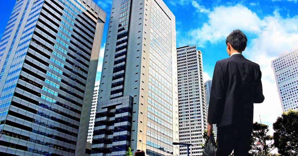 高層ビル群の前にたつスーツ姿の男性の後ろ姿