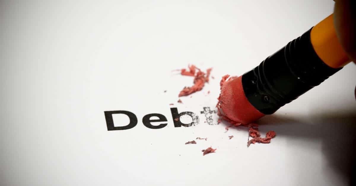 Debt借金という文字を鉛筆のお尻の消しゴムで消している