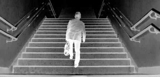 階段を上がるスーツ姿の男性 白黒反転