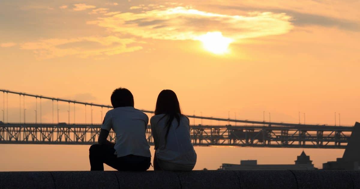 夕日を見ながら土手に並んで座るカップル