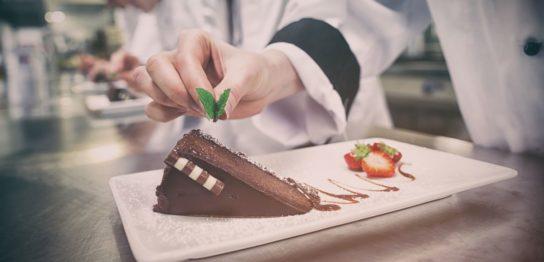 ケーキを盛り付けるパティシエの腕