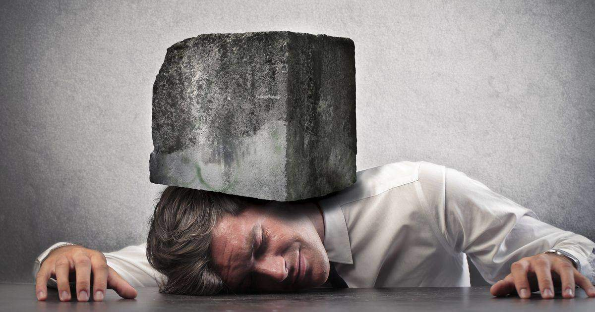 重いブロックに押しつぶされる男